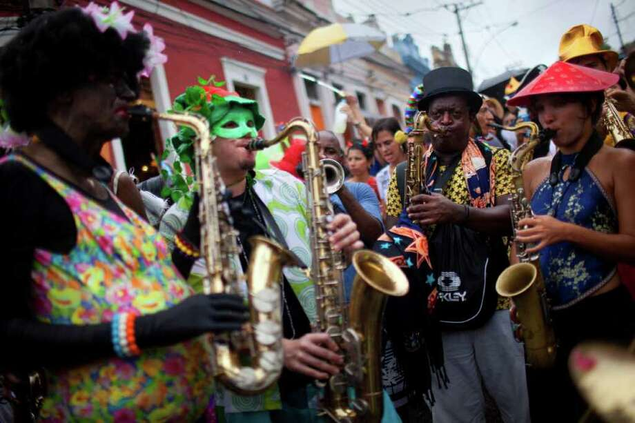 "Members of a band perform during a ""Ceu na Terra"" street parade in Rio de Janeiro, Brazil, Saturday, March 5, 2011. The five-day annual carnival celebration officially started Friday and is expected to draw about 756,000 visitors, both foreign and Brazilian, who will pack hotels to nearly 100 percent capacity and spend about $559 million, according to Rio state's tourism department. (AP Photo/Felipe Dana) Photo: Felipe Dana, AP / Associated Press"