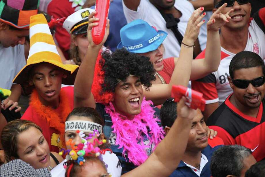 """People dance during a """"Bola Preta"""" block parade in Rio de Janeiro, Brazil, Saturday, March 5, 2011. The five-day annual carnival celebration officially started Friday and is expected to draw about 756,000 visitors, both foreign and Brazilian, who will pack hotels to nearly 100 percent capacity and spend about $559 million, according to Rio state's tourism department. (AP Photo/Silvia Izquierdo) Photo: Silvia Izquierdo, AP / Associated Press"""