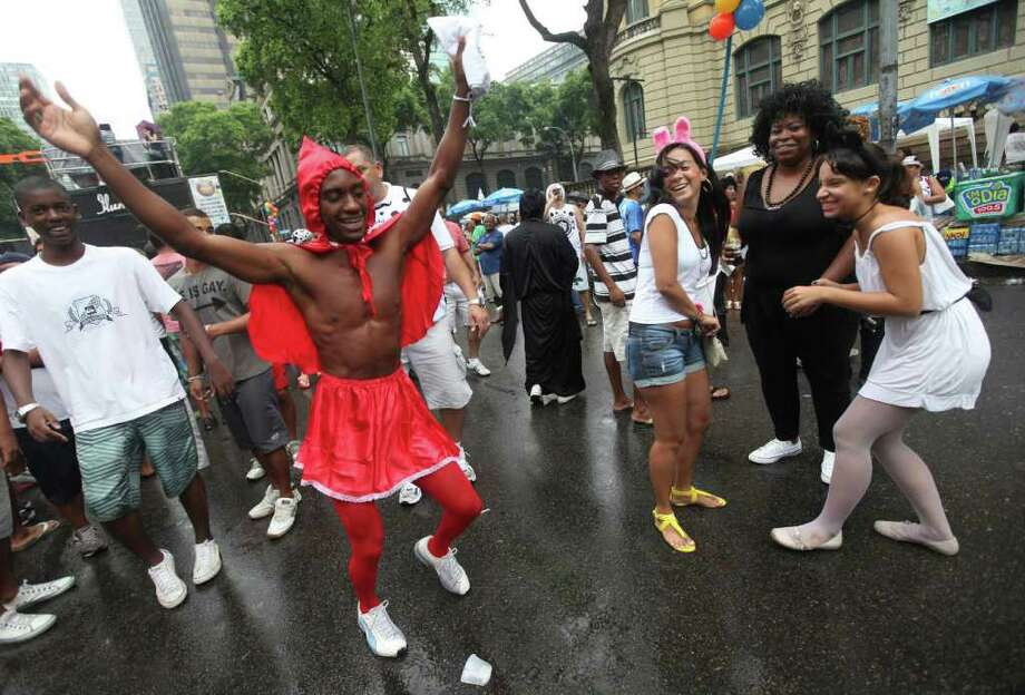 "A man dances during a ""Bola Preta"" block parade in Rio de Janeiro, Brazil, Saturday, March 5, 2011. The five-day annual carnival celebration officially started Friday and is expected to draw about 756,000 visitors, both foreign and Brazilian, who will pack hotels to nearly 100 percent capacity and spend about $559 million, according to Rio state's tourism department. (AP Photo/Silvia Izquierdo) Photo: Silvia Izquierdo, AP / Associated Press"
