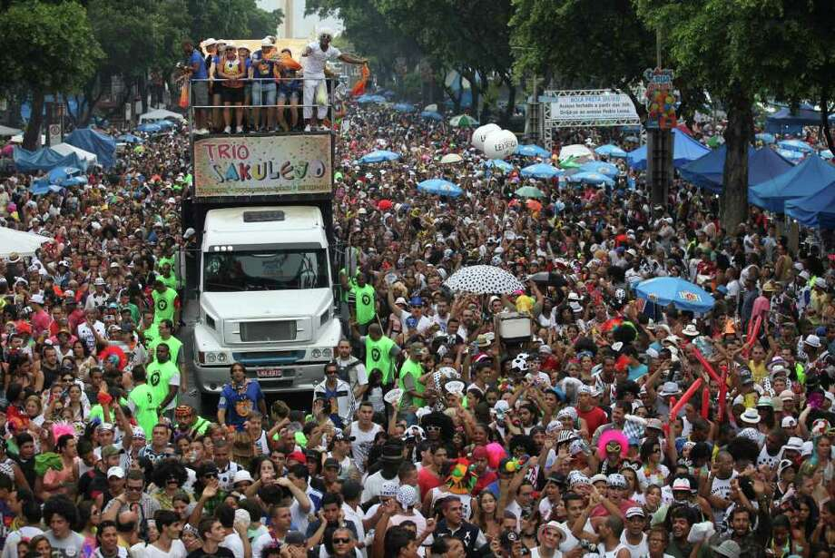 "People dance during a ""Bola Preta"" block parade in Rio de Janeiro, Brazil, Saturday, March 5, 2011. The five-day annual carnival celebration officially started Friday and is expected to draw about 756,000 visitors, both foreign and Brazilian, who will pack hotels to nearly 100 percent capacity and spend about $559 million, according to Rio state's tourism department. (AP Photo/Silvia Izquierdo) Photo: Silvia Izquierdo, AP / Associated Press"