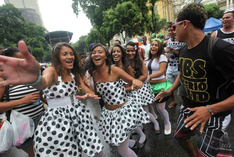 "Women dance during a ""Bola Preta"" block parade in Rio de Janeiro, Brazil, Saturday, March 5, 2011. The five-day annual carnival celebration officially started Friday and is expected to draw about 756,000 visitors, both foreign and Brazilian, who will pack hotels to nearly 100 percent capacity and spend about $559 million, according to Rio state's tourism department. (AP Photo/Silvia Izquierdo) Photo: Silvia Izquierdo, AP / Associated Press"