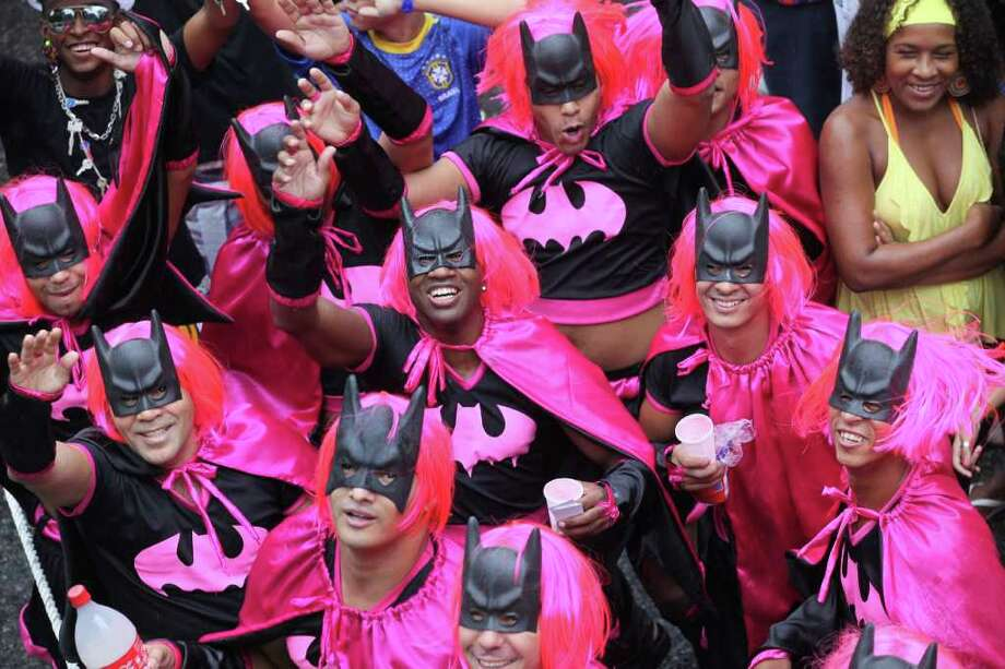 "Men, disguised as ""Batman,"" dance during a ""Bola Preta"" block parade in Rio de Janeiro, Brazil, Saturday, March 5, 2011. The five-day annual carnival celebration officially started Friday and is expected to draw about 756,000 visitors, both foreign and Brazilian, who will pack hotels to nearly 100 percent capacity and spend about $559 million, according to Rio state's tourism department. (AP Photo/Silvia Izquierdo) Photo: Silvia Izquierdo, ASSOCIATED PRESS / Associated Press"
