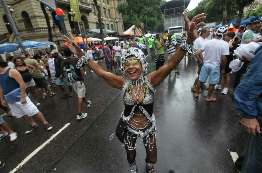 "A woman dances during a ""Bola Preta"" block parade in Rio de Janeiro, Brazil, Saturday, March 5, 2011. The five-day annual carnival celebration officially started Friday and is expected to draw about 756,000 visitors, both foreign and Brazilian, who will pack hotels to nearly 100 percent capacity and spend about $559 million, according to Rio state's tourism department. (AP Photo/Silvia Izquierdo) Photo: Silvia Izquierdo, AP / Associated Press"