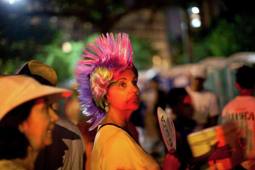 A reveler looks at people dance during a carnival parade in Rio de Janeiro, Brazil, Friday, March 4,