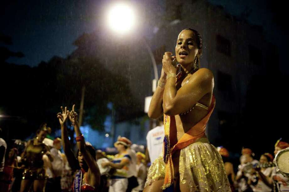 A revealer dances under the rain during a carnival parade in Rio de Janeiro, Brazil, Friday March 4, 2011. The five-day annual carnival celebration officially starts Friday and is expected to draw about 756,000 visitors, both foreign and Brazilian, who will pack hotels to nearly 100 percent capacity and spend about $559 million, according to Rio state's tourism department. (AP Photo/Rodrigo Abd) Photo: Rodrigo Abd, ASSOCIATED PRESS / Associated Press