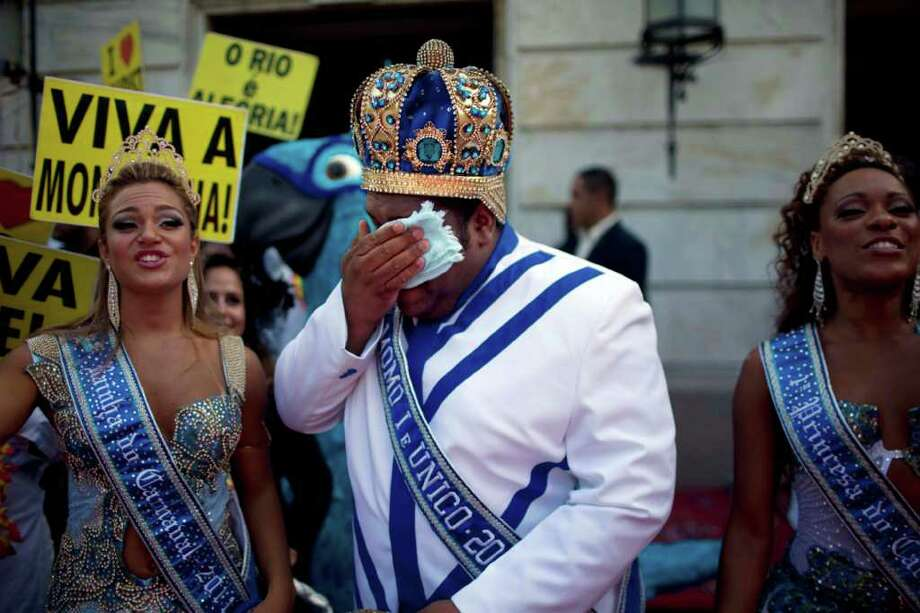 This year's King Momo, the crowned and costumed Milton Rodrigues, center, flanked by the Carnival queen and a princess, wipes his faces during carnival celebrations in Rio de Janeiro, Brazil, Friday, March 4, 2011. Covered in confetti and to the sound of drums, Rio's mayor Eduardo Paes handed the key to the city to King Momo, the mythical figure who reigns over the chaos of Carnival, officially opening this seaside city's five-day annual exaltation of music, booze and flesh. (AP Photo/Rodrigo Abd) Photo: Rodrigo Abd, ASSOCIATED PRESS / Associated Press