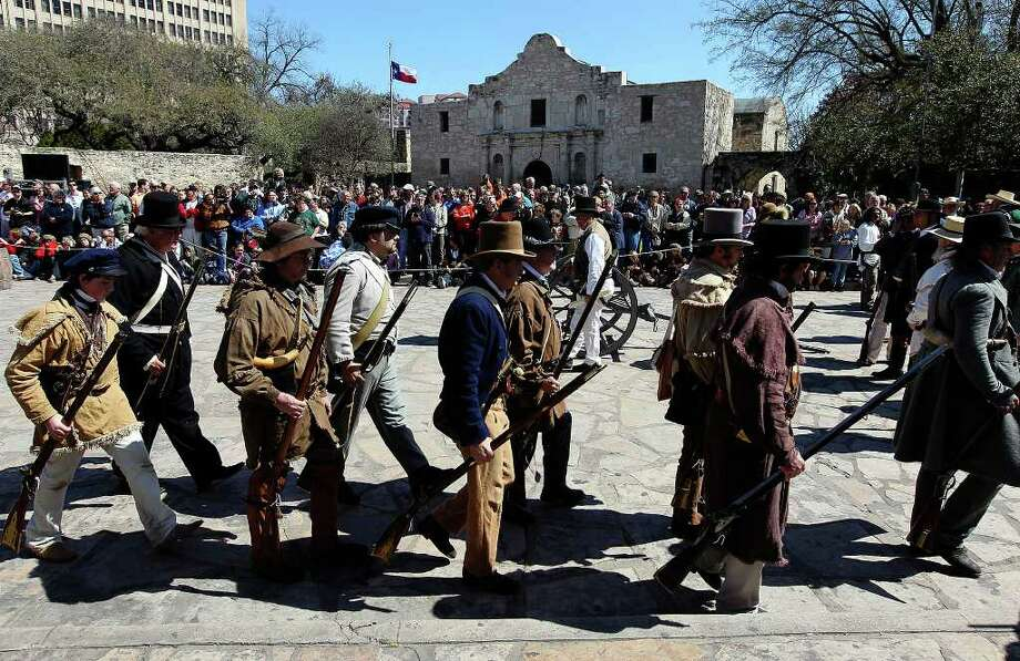 The re-enactment of the battle at the Alamo is watched by hundreds of people lining Alamo Plaza on Saturday, Mar. 5, 2011. Re-enactors dressed in period costumes for the event marked the 175th anniversary of the battle. Photo: KIN MAN HUI, Kin Man Hui/kmhui@express-news.net / San Antonio Express-News