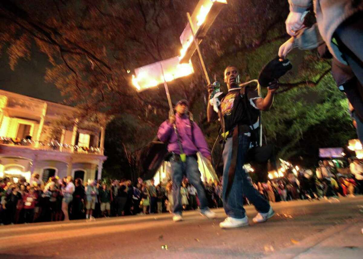 In this March 3, 2011 photo, a flambeau accepts a tip from a reveler during the Krewe of Chaos Mardi Gras parade on St. Charles Ave. in New Orleans. The crescent city expects its largest crowd for the annual celebration since Hurricane Katrina struck in 2005. (AP Photo/Gerald Herbert)