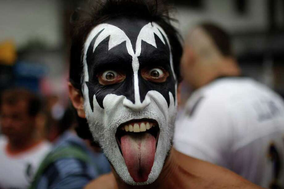 "A reveler, with his face painted as musical group Kiss member Gene Simons, sticks his tongue out during the ""Carmelitas"" street carnival parade in Rio de Janeiro, Brazil, Friday, March 4, 2011. ""Carmelitas"" is a band started in 1991 by a group of friends who gathered for soccer and drinks just outside a convent of Carmelite nuns. Jokes about the possibility of nuns escaping to join the party gave rise to the band, which parades twice: once at the beginning of Carnival, when the nuns escape the convent to join the fun, and then on the last day, when they return to their cloistered existence. (AP Photo/Felipe Dana) Photo: Felipe Dana, ASSOCIATED PRESS / Associated Press"