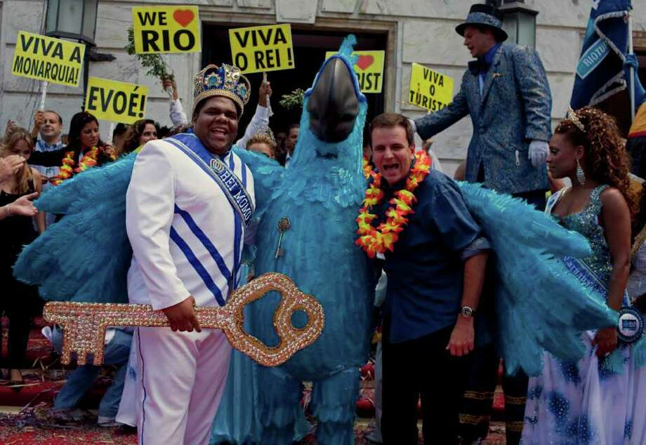 Holding the key to the city, this year's King Momo, the crowned and costumed Milton Rodrigues, left, accompanied by a person disguised as Blu, a character of a Brazilian-American computer-animated film, center, and Rio's mayor Eduardo Paes, right, poses for pictures during carnival celebrations in Rio de Janeiro, Brazil, Friday, March 4, 2011. Covered in confetti and to the sound of drums, Rio's mayor Eduardo Paes handed the key to the city to King Momo, the mythical figure who reigns over the chaos of Carnival, officially opening this seaside city's five-day annual exaltation of music, booze and flesh. (AP Photo/Rodrigo Abd) Photo: Rodrigo Abd, ASSOCIATED PRESS / Associated Press
