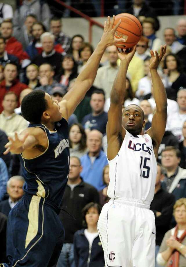 Connecticut's Kemba Walker, right, shoots past Notre Dame's Tyrone Nash during the first half of an NCAA college basketball game in Storrs, Conn., on Saturday, March. 5, 2011.  (AP Photo/Fred Beckham) Photo: AP