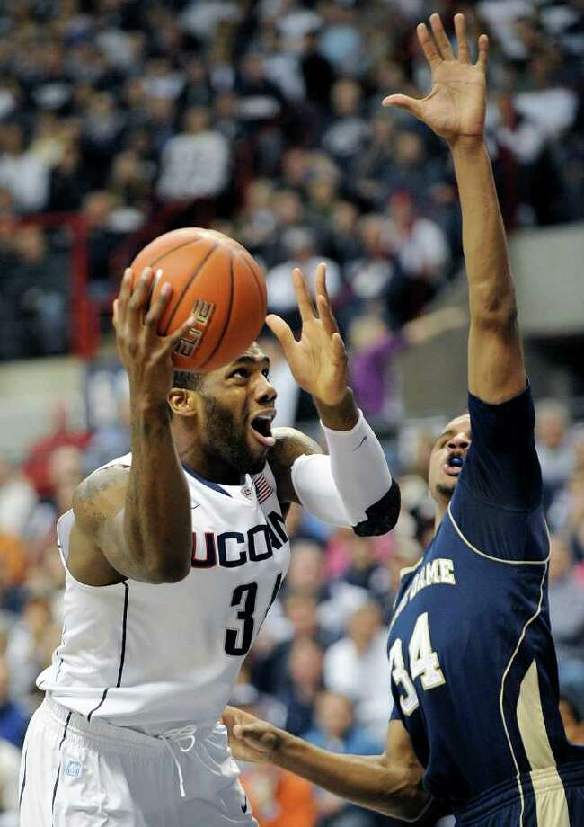 Connecticut's Alex Oriakhi, left, drives past Notre Dame's Carleton Scott during the first half of an NCAA college basketball game in Storrs, Conn., on Saturday, March. 5, 2011.  (AP Photo/Fred Beckham) Photo: AP