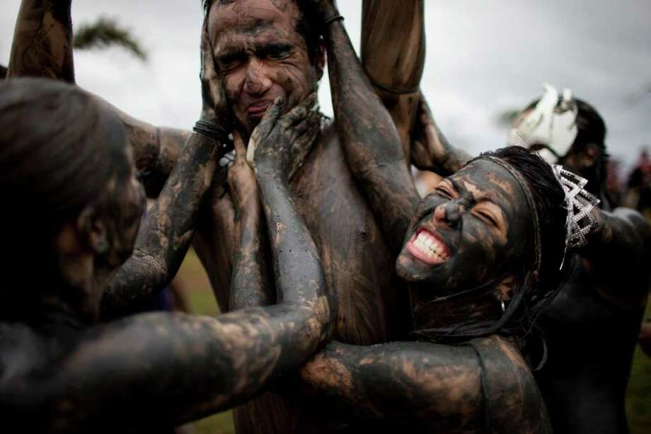 Members of the the 'Bloco da Lama', or Mud Block carnival group, cover a man in mud during carnival celebrations in Paraty, Brazil, Saturday, March 5,  2011. Brazil's official carnival is held this year March 4-8.  (AP Photo/Rodrigo Abd) Photo: AP
