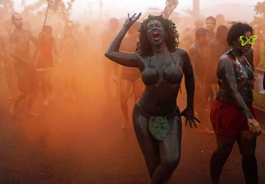 A woman dances amid orange smoke during the 'Bloco da Lama', or Mud Block carnival group parade in Paraty, Brazil, Saturday, March 5,  2011. Brazil's official carnival is held this year March 4-8. (AP Photo/Rodrigo Abd) Photo: AP
