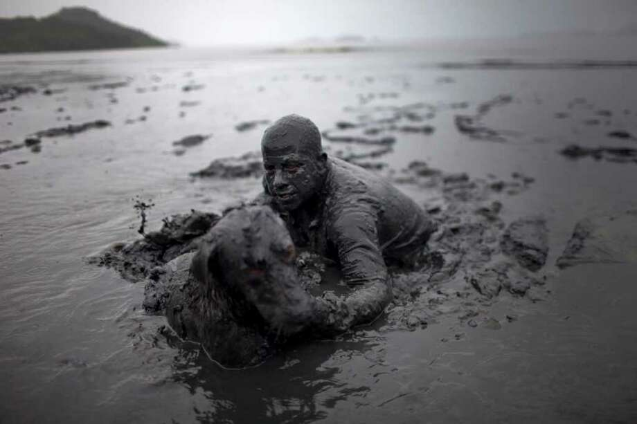 A man and his dog cover walk out after covering in mud as part of the 'Bloco da Lama', or Mud Block carnival group in Paraty, Brazil, Saturday, March 5,  2011. Brazil's official carnival is held this year March 4-8. (AP Photo/Rodrigo Abd) Photo: AP