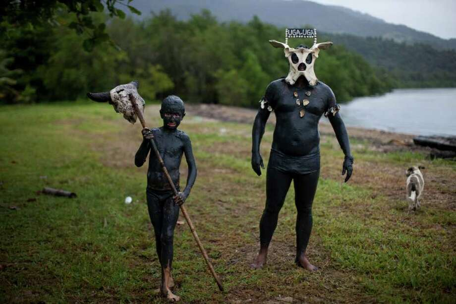 Revelers of the 'Bloco da Lama', or Mud Block, carnival group, walk covered in mud before a carnival parade in Paraty, Brazil, Saturday, March 5,  2011. (AP Photo/Rodrigo Abd) Photo: AP
