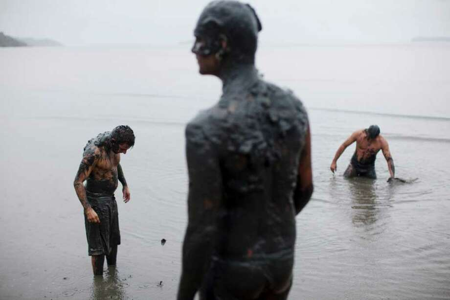 People gather in a mud swamp at a mud party during Carnival celebrations in Paraty,  Brazil, Saturday, March 5,  2011. The five-day annual carnival celebration officially started Friday and is expected to draw about 756,000 visitors, both foreign and Brazilian, who will pack hotels to nearly 100 percent capacity and spend about $559 million, according to Rio state's tourism department. (AP Photo/Rodrigo Abd) Photo: AP