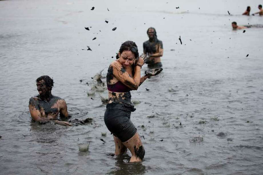 People participate in a mud party during Carnival celebrations in Paraty,  Brazil, Saturday, March 5,  2011. The five-day annual carnival celebration officially started Friday and is expected to draw about 756,000 visitors, both foreign and Brazilian, who will pack hotels to nearly 100 percent capacity and spend about $559 million, according to Rio state's tourism department. (AP Photo/Rodrigo Abd) Photo: AP