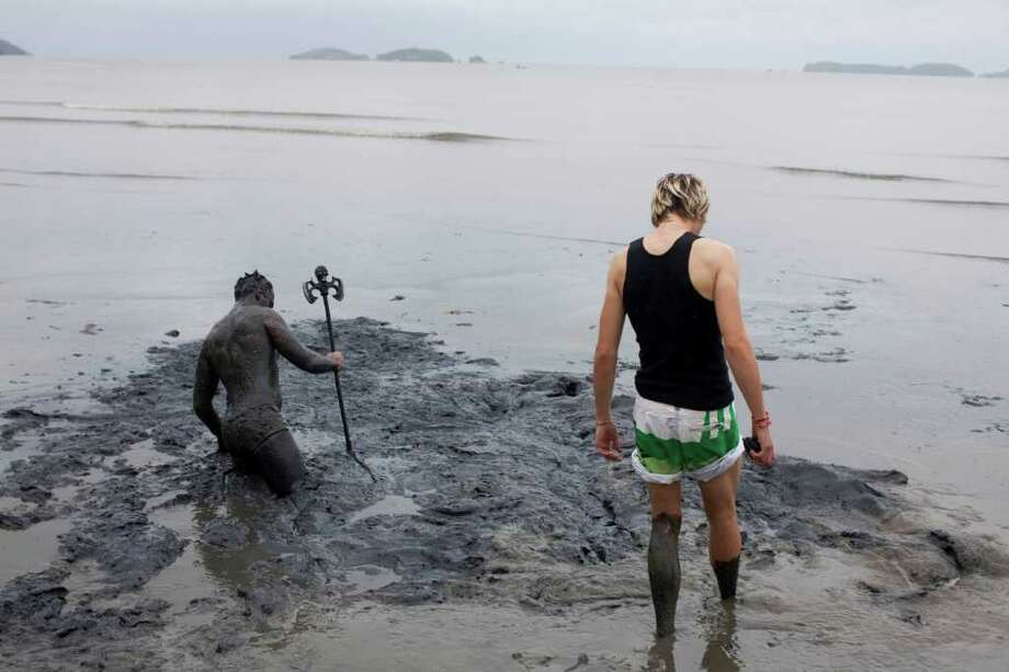 Two men walk into a mud swamp at a mud party during Carnival celebrations in Paraty,  Brazil, Saturday, March 5,  2011. The five-day annual carnival celebration officially started Friday and is expected to draw about 756,000 visitors, both foreign and Brazilian, who will pack hotels to nearly 100 percent capacity and spend about $559 million, according to Rio state's tourism department. (AP Photo/Rodrigo Abd) Photo: AP