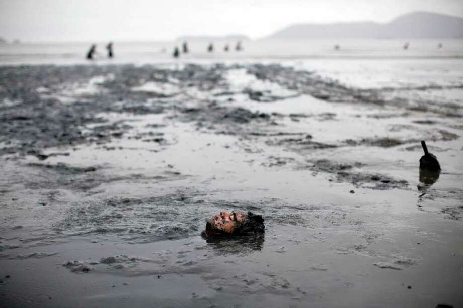 A man lies in a mud swamp at a mud party during Carnival celebrations in Paraty,  Brazil, Saturday, March 5,  2011. The five-day annual carnival celebration officially started Friday and is expected to draw about 756,000 visitors, both foreign and Brazilian, who will pack hotels to nearly 100 percent capacity and spend about $559 million, according to Rio state's tourism department. (AP Photo/Rodrigo Abd) Photo: AP