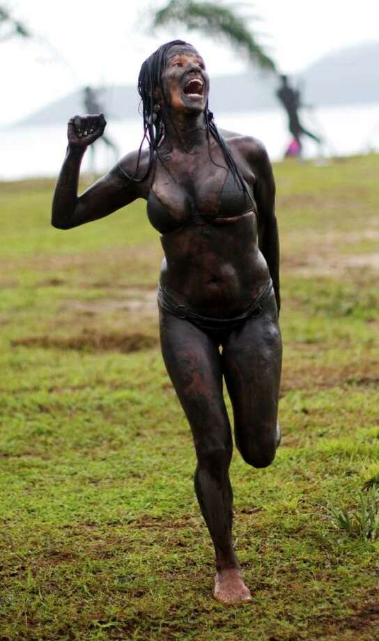Covered by mud, a woman dances at a mud party during Carnival celebrations in Paraty,  Brazil, Saturday, March 5,  2011. The five-day annual carnival celebration officially started Friday and is expected to draw about 756,000 visitors, both foreign and Brazilian, who will pack hotels to nearly 100 percent capacity and spend about $559 million, according to Rio state's tourism department. (AP Photo/Rodrigo Abd) Photo: AP