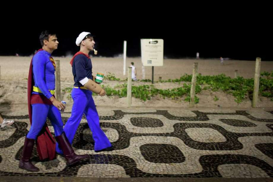 Revelers dressed as cartoon heroes Superman, left, and Popeye, walk along Ipanema beach during the 'Banda de Ipanema' street parade in Rio de Janeiro, Brazil, Saturday, March 5, 2011. The five-day annual carnival celebration officially started Friday and is expected to draw about 756,000 visitors, both foreign and Brazilian, who will pack hotels to nearly 100 percent capacity and spend about $559 million, according to Rio state's tourism department. (AP Photo/Felipe Dana) Photo: AP