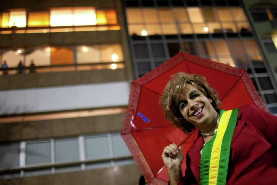 A reveler who wears a homemade Brazilian presidential sash as she imitates Brazil's President Dilma Rousseff, smiles during the 'Banda de Ipanema' street parade in Rio de Janeiro, Brazil, Saturday, March 5, 2011. The five-day annual carnival celebration officially started Friday and is expected to draw about 756,000 visitors, both foreign and Brazilian, who will pack hotels to nearly 100 percent capacity and spend about $559 million, according to Rio state's tourism department. (AP Photo/Felipe Dana) Photo: AP