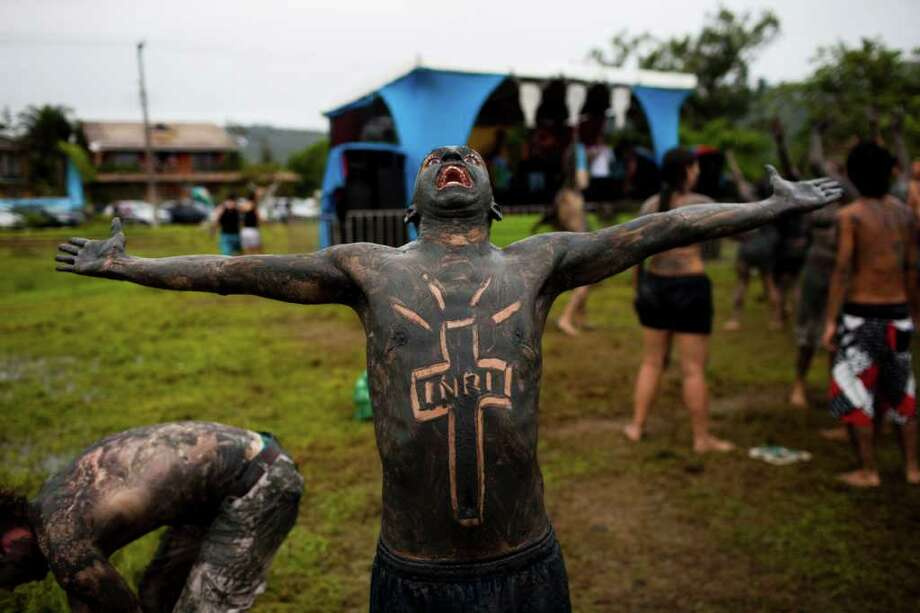 A member of the 'Bloco da Lama', or Mud Block carnival group, gestures during carnival celebrations in Paraty, Brazil, Saturday, March 5,  2011. Brazil's official carnival is held this year March 4-8. (AP Photo/Rodrigo Abd) Photo: AP