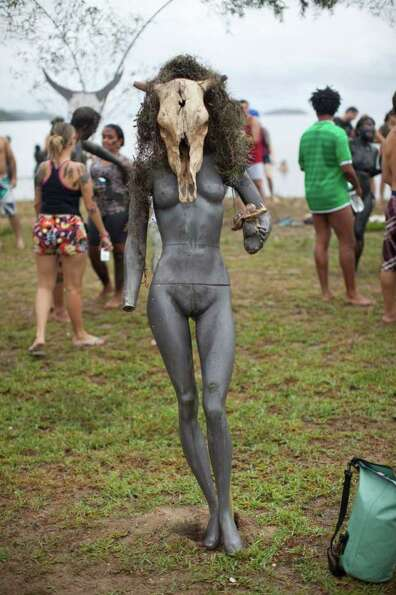 A mannequin wearing an animal skull, stands amid revelers during carnival celebrations in Paraty, Br