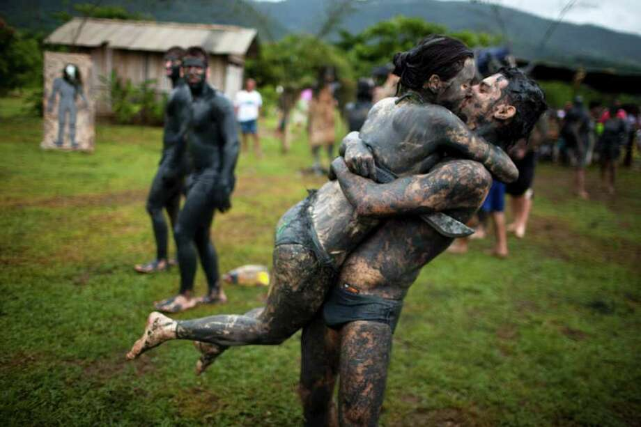 A couple, member of the 'Bloco da Lama', or Mud Block carnival group, kisses during carnival celebrations in Paraty, Brazil, Saturday, March 5,  2011. Brazil's official carnival is held this year March 4-8 . (AP Photo/Rodrigo Abd) Photo: AP