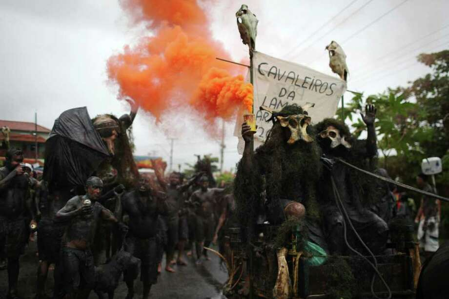 Revelers perform during the 'Bloco da Lama', or Mud Block carnival group parade in Paraty, Brazil, Saturday, March 5,  2011. Brazil's official carnival is held this year March 4-8. (AP Photo/Rodrigo Abd) Photo: AP