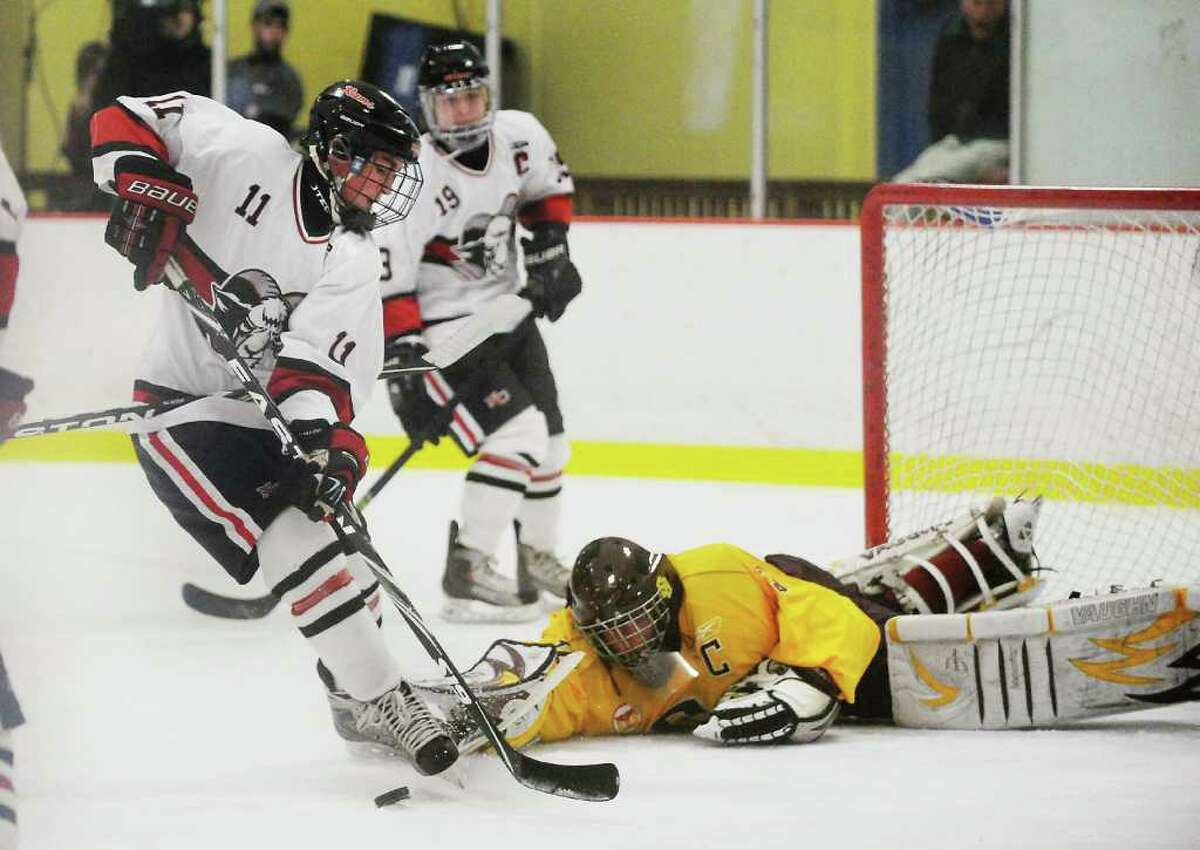 New Canaan's Charlie Corcoran takes a shot on goal against St. Joseph's Ron Johnson in the boys hockey FCIAC championship game at Terry Conners Rink in Stamford, Conn. on Saturday March 5, 2011.