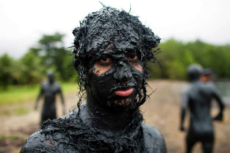 A man stands next to a mangrove after covering himself in mud during carnival celebrations in Paraty, Brazil, Saturday, March 5,  2011. Brazil's official carnival is held this year March 4-8. (AP Photo/Rodrigo Abd) Photo: AP