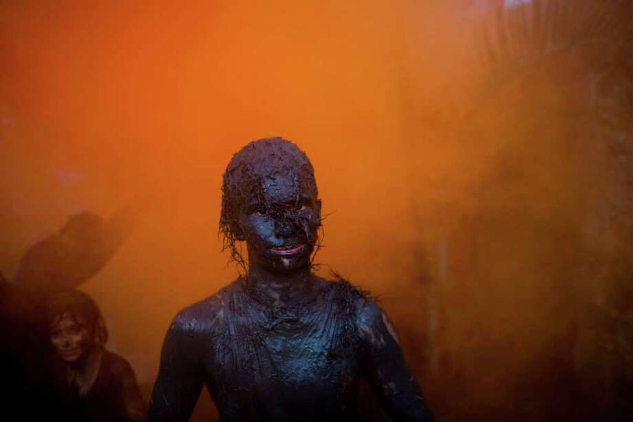 Covered by mud, a man parades at a mud party during Carnival celebrations in Paraty,  Brazil, Saturday, March 5,  2011. The five-day annual carnival celebration officially started Friday and is expected to draw about 756,000 visitors, both foreign and Brazilian, who will pack hotels to nearly 100 percent capacity and spend about $559 million, according to Rio state's tourism department. (AP Photo/Rodrigo Abd) Photo: AP