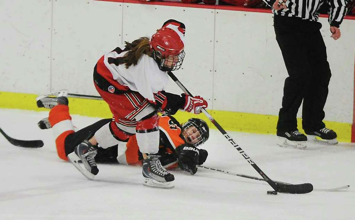 New Canaan's Holly Burwick takes the puck from Ridgefield's Erica Guider in the girls hockey state championship game at Terry Conners Rink in Stamford, Conn. on Saturday March 5, 2011.