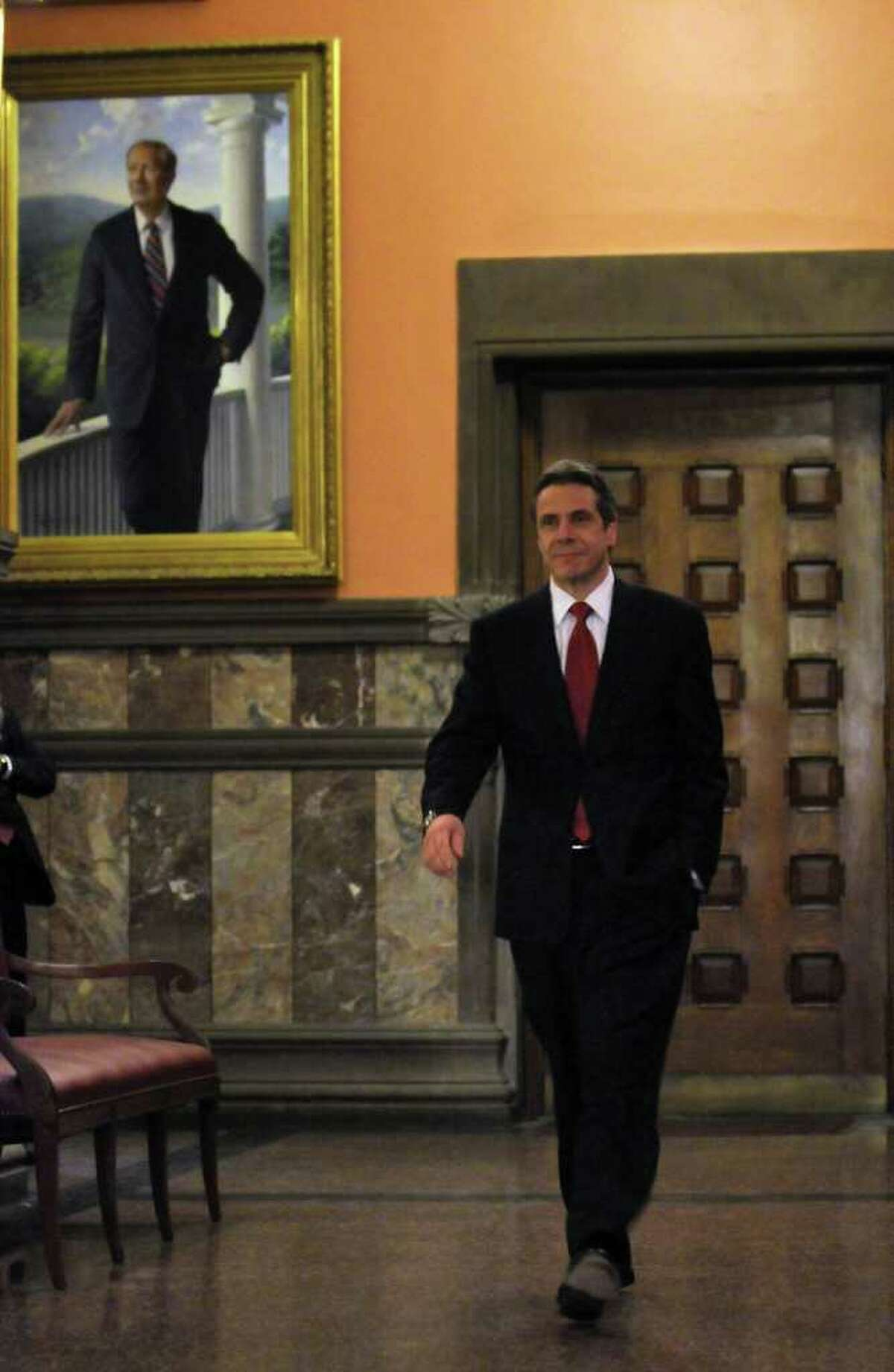 Governor Andrew Cuomo walks near a painting of former Governor George Pataki, left, outside of his second floor office to discuss Monday's opening day of the legislative session in the Capitol in Albany, NY on January 10, 2011. ( Philip Kamrass / Times Union )