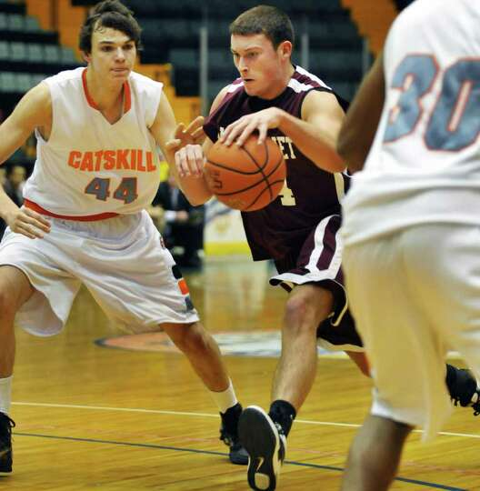 Watervliet's #44 Dan Nittinger, center, drives through  Catskill's #44 Liam Roberts, left, and #30 J