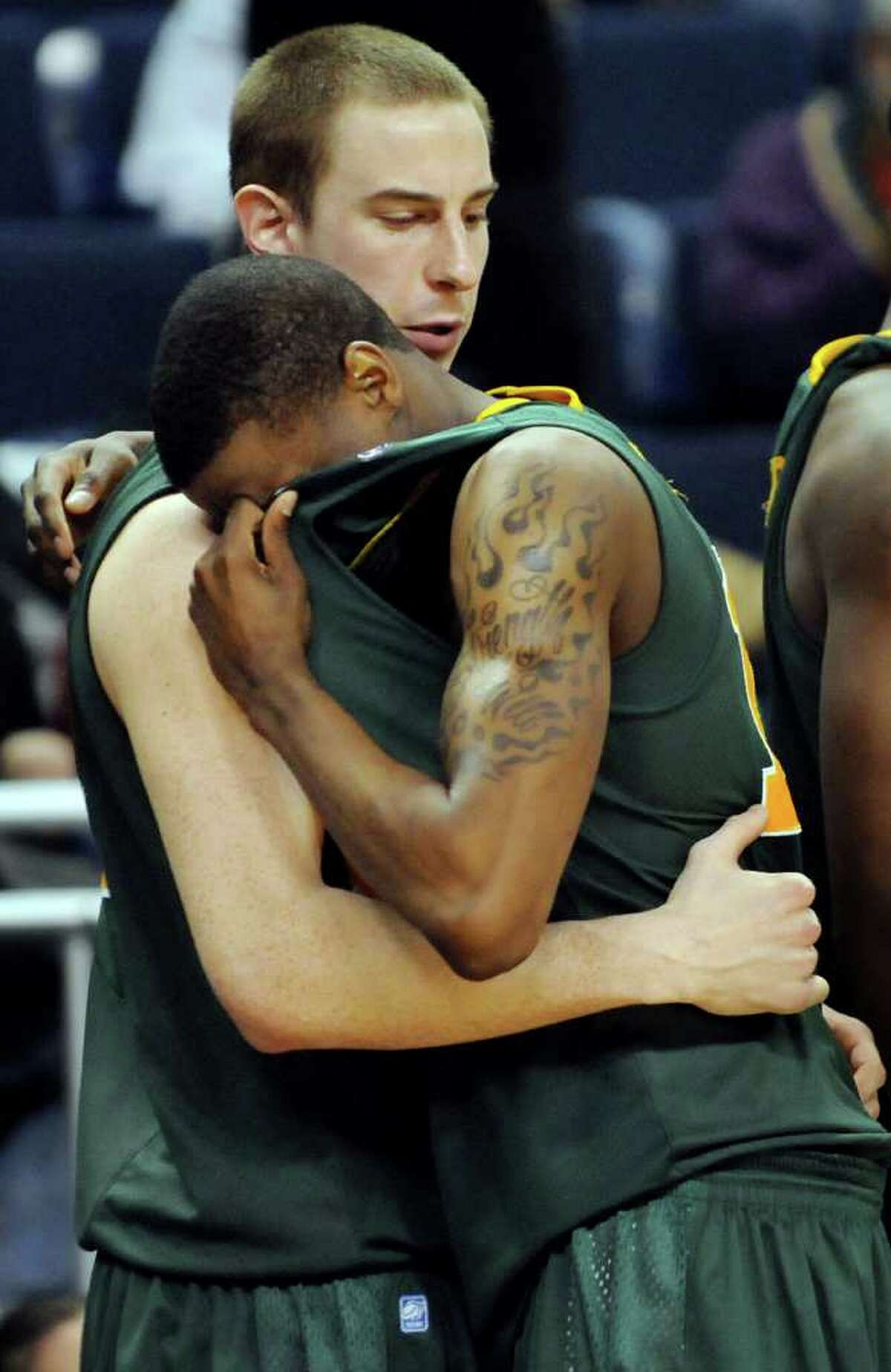 Siena's Clarence Jackson, right, is consoled by teammate Owen Wignot when they lose to Iona in their basketball game at the MAAC Championships on Saturday, March 5, 2011, at Webster Bank Arena at Harbor Yard in Bridgeport, Conn. (Cindy Schultz / Times Union)