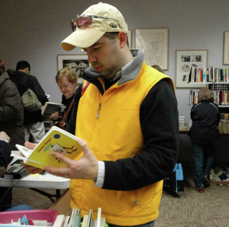 Tim Keefe, of Norwalk had gone to the Westport Public Library on Saturday to return books his children had borrowed. When he learned the annual winter book sale was going on, he decided to browse through the stacks of books. Photo: Meg Barone / Westport News freelance