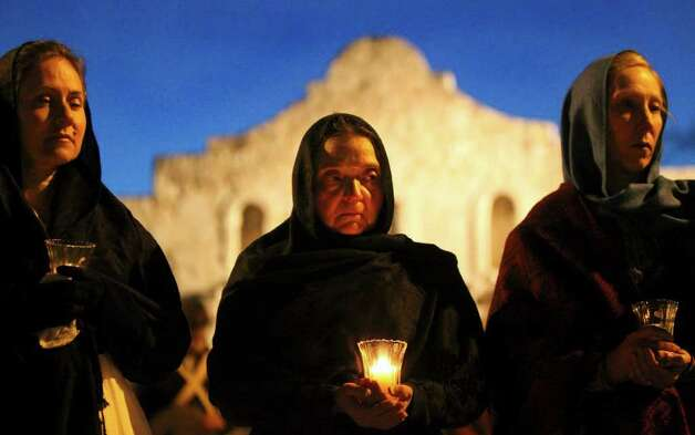 Shirley Schmidt (center) of Indianapolis, Indiana holds a candle with women in front of the Alamo during the Dawn at the Alamo event held Sunday March 6, 2011. Thirteen women stood vigil Sunday in front of the Texas shrine representing each day of the siege in 1836. JOHN DAVENPORT/jdavenport@express-news.net Photo: JOHN DAVENPORT, SAN ANTONIO EXPRESS-NEWS / jdavenport@express-news.net