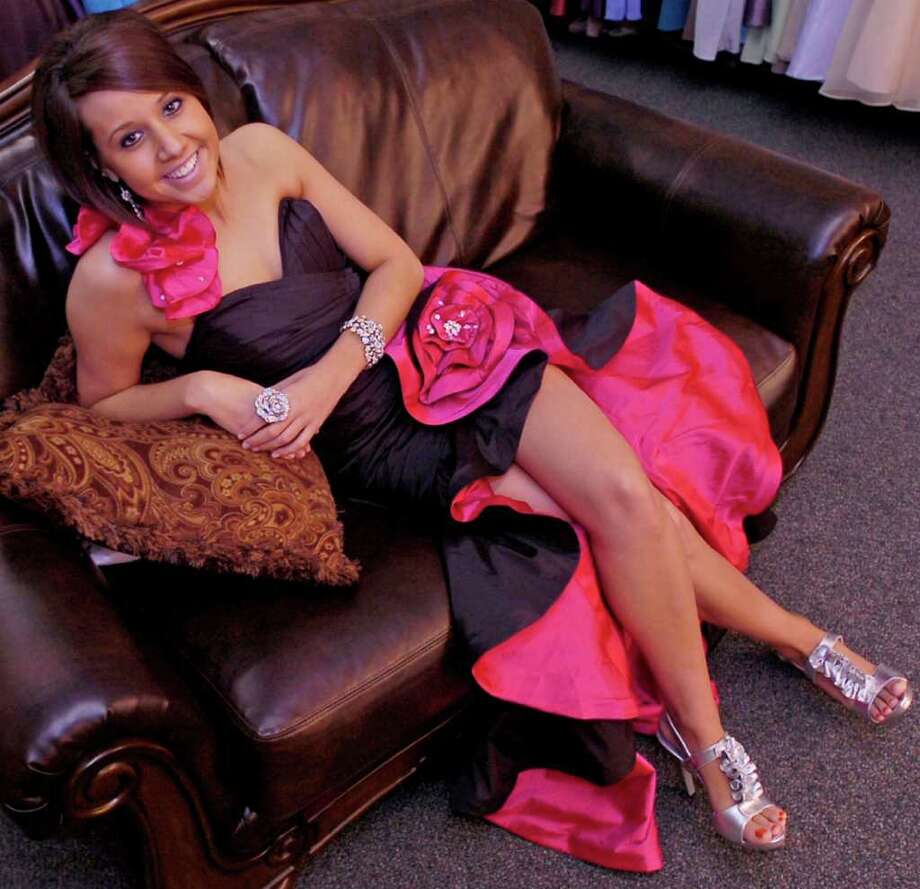 Katelyn Broussard models a Mori Lee one-shoulder gown for $328. This flamenco-inspired gown is sophisticated while being fun. One thing to remember about high-lows are the shoes. If the shoe doesn't pull it together, the effect will fall apart. Dave Ryan/The Enterprise Photo: Dave Ryan / Beaumont