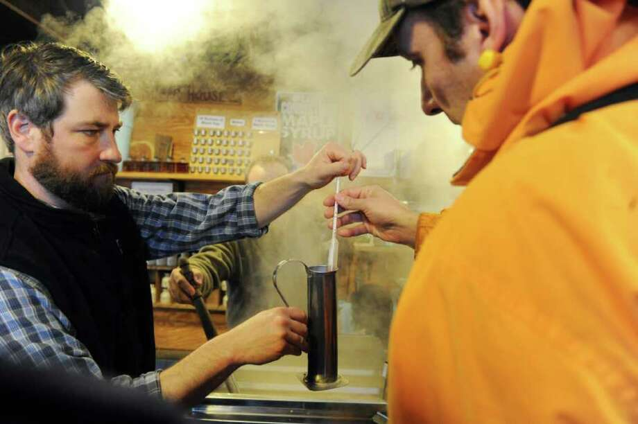 Will Kies, left, Director of Education at the Stamford Museum and Nature Center, shows Dino Psichopaidas a hydrometer which is used to measure the thickness of syrup during Maple Sugar Sunday the center in Stamford, Conn., March 6, 2011. Maple Syrup Sunday is an annual event focusing on the deeply rooted New England tradition of maple sugaring. Photo: Keelin Daly / Stamford Advocate