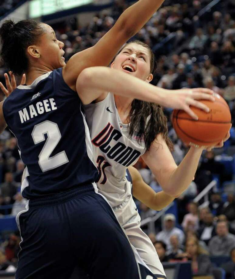 Connecticut's Stefanie Dolson, right, is fouled by Georgetown's Tia Magee during the first half of a quarterfinal NCAA college basketball game at the Big East Conference Championships in Hartford, Conn., Sunday, March 6, 2011. (AP Photo/Jessica Hill) Photo: AP