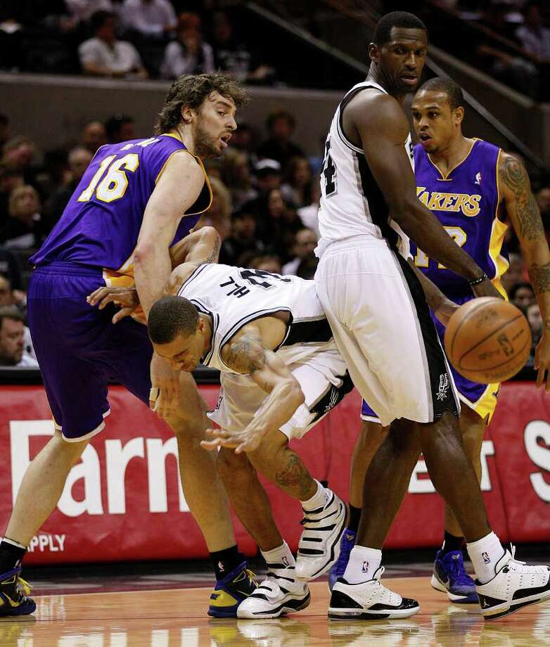 SPURS – Under pressure from Los Angeles Lakers guard Shannon Brown, right, San Antonio Spurs guard George Hill loses control of the ball as he tries to squeeze between Antonio McDyess and Paul Gasol, during the first half at the AT&T Center, Sunday, March 6, 2011. JERRY LARA/glara@express-news.net Photo: JERRY LARA, San Antonio Express-News / SAN ANTONIO EXPRESS-NEWS (NFS)