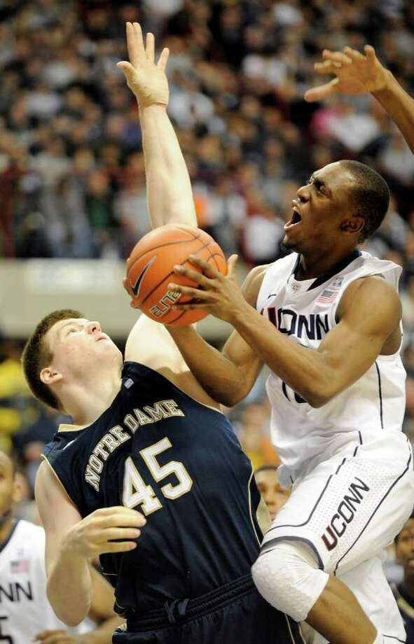 Connecticut's Kemba Walker, right, drives past Notre Dame's Jack Cooley during the second half of Connecticut's 70-67 loss in an NCAA college basketball game in Storrs, Conn., on Saturday, March. 5, 2011. Walker scored a game-high 34 points in the defeat. (AP Photo/Fred Beckham) Photo: AP