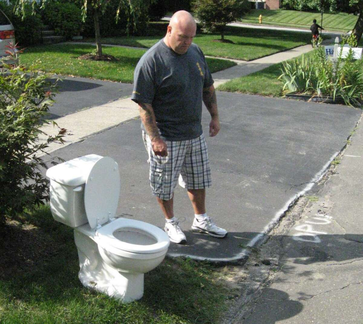 Grant Dalling of 385 Bunnyview Drive, Stratford, looks at snowplow damage to his driveway that the town has yet to repair. The toilet is his message of silent protest to Stratford officials.