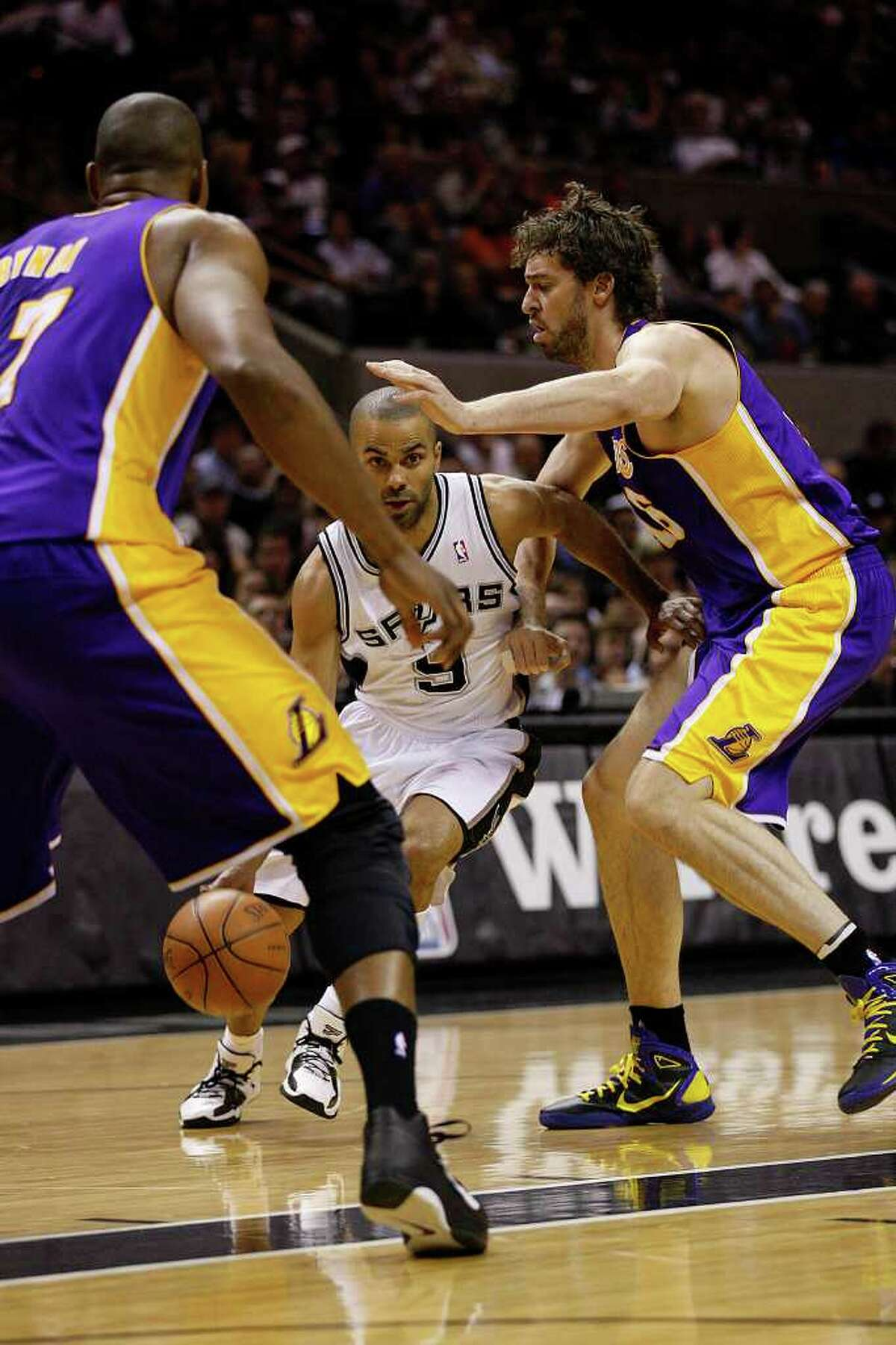 SPURS -- San Antonio Spurs Tony Parker tries to split the defense of Los Angeles Lakers Andrew Bynum, left, and Pau Gasol, during the first half at the AT&T Center, Sunday, March 6, 2011. JERRY LARA/glara@express-news.net