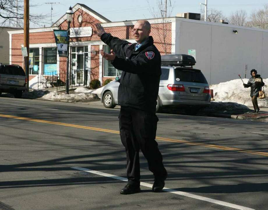 Fairfield Police department Special Agent Sean Grabowski directs a car out of a difficult parking lot onto the Post Road in downtown Fairfield on Monday, Feb. 14, 2011. Grabowski walks the downtown area assisting people, checking parking, and making sure that businesses are secured in the evening. Photo: B.K. Angeletti / Connecticut Post