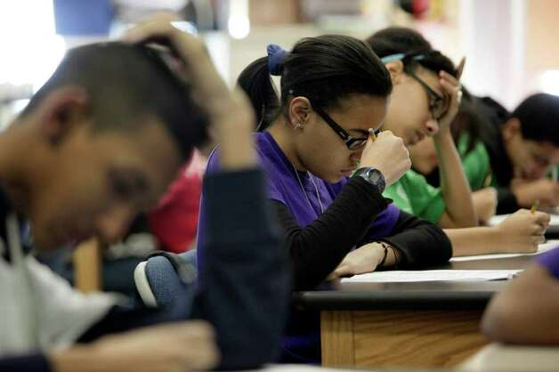 In a March 3, 2011 photo, students take a test during a Global History class at the Washington Heights Expeditionary Learning School, in New York.  As Mayor Michael Bloomberg plans to take more than 6,000 teachers off the payroll to help balance a strained budget, some parent advocates are questioning what the layoffs will do to New York public school class sizes.  (AP Photo/Richard Drew) Photo: Richard Drew
