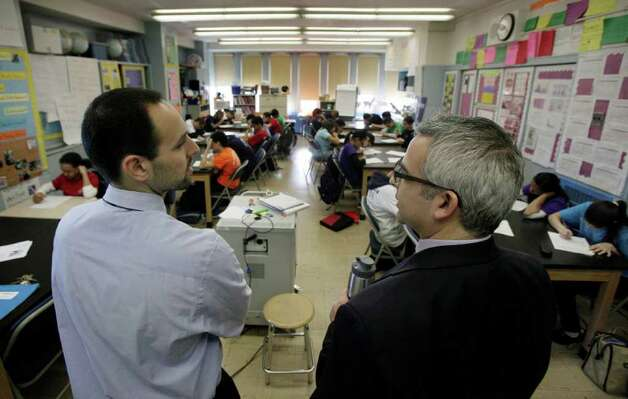 In a March 3, 2011 photo, teacher Josh Krinsky, left, and Principal Brett Kimmel get together in Krinsky's Global History class the Washington Heights Expeditionary Learning School, in New York.  As Mayor Michael Bloomberg plans to take more than 6,000 teachers off the payroll to help balance a strained budget, some parent advocates are questioning what the layoffs will do to New York public school class sizes.  (AP Photo/Richard Drew) Photo: Richard Drew
